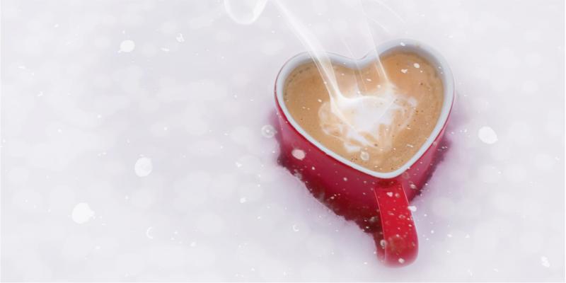 Sydämen muotoinen, kuuma kaakaomuki lumihangessa
